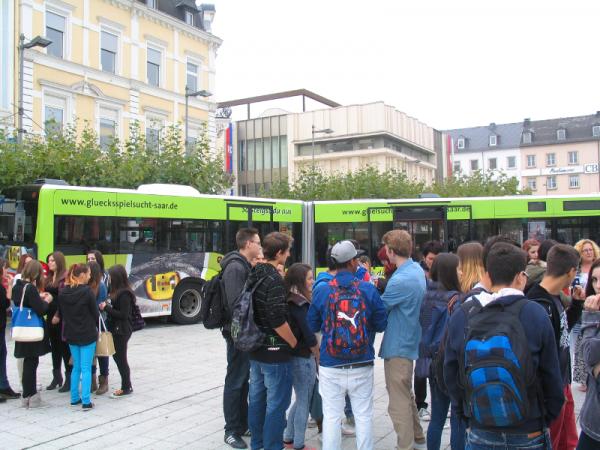 """Schüler des TGBBZ Saarlouis vor dem neu gestalteten Bus mit der Aufschrift: """"Mach das Soiel nicht länger mit!"""