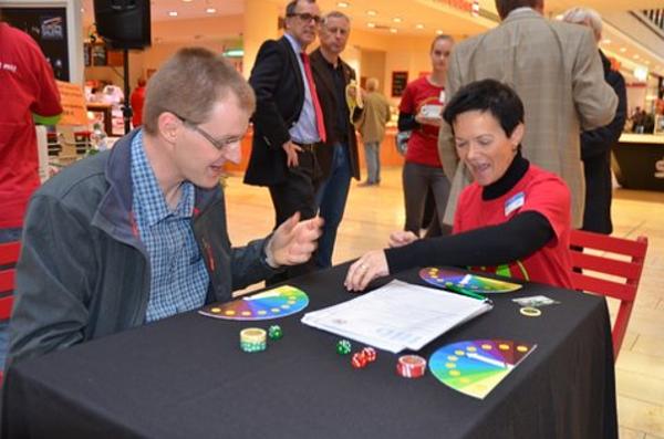 Frau Klein vom Gesundheitsamt erklärt die Risiken des Glücksspiels anhand der Bank of Winner